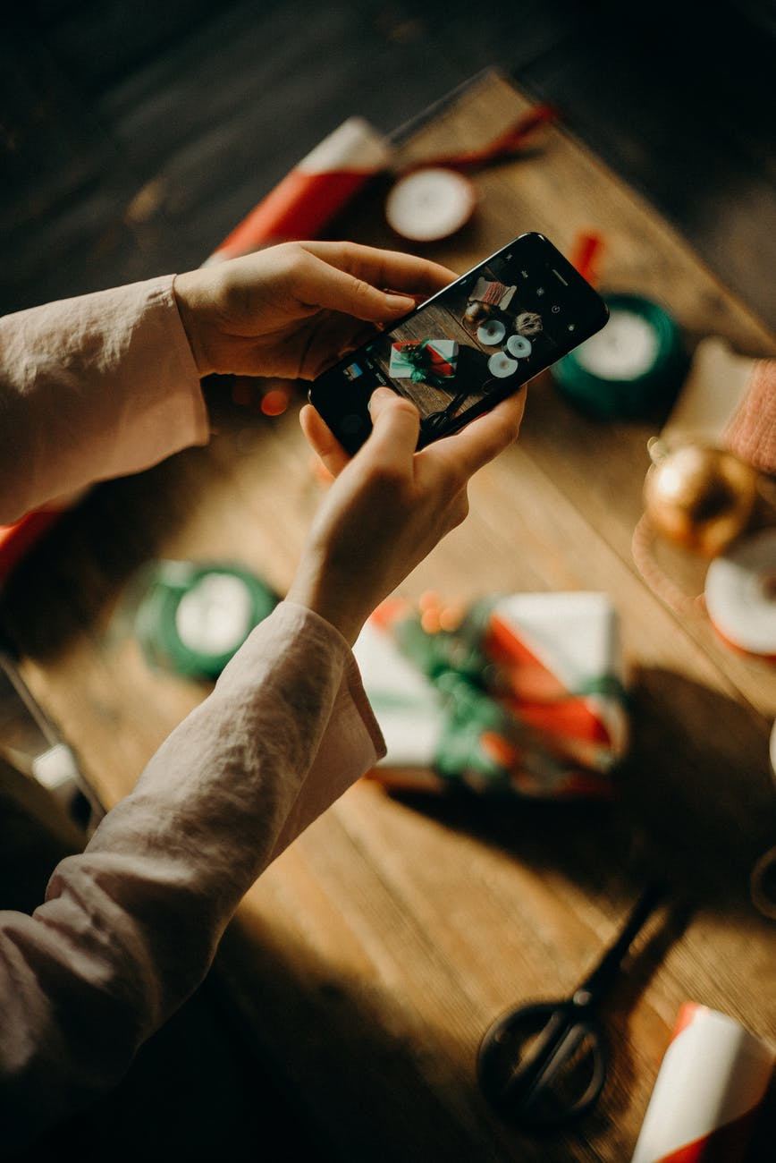 selective focus photography of person taking photo of table
