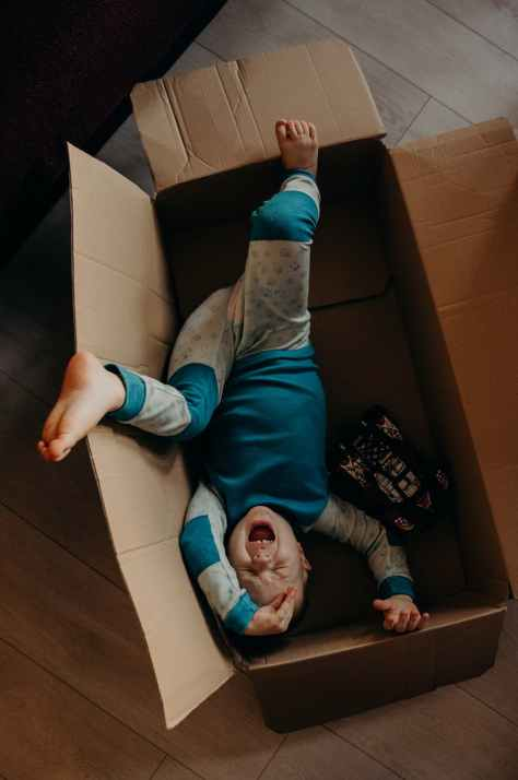 little boy crying inside a box